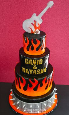Kiss themed, rocker inspired wedding cake complete with flames, spikes and a chocolate guitar cake topper.  www.gimmesomesugarLV.com