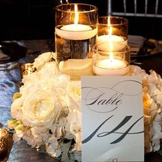 The low centerpieces included floating candles surrounded by flowers and the table number. Victoria Clausen Florals and Event Design @Victoria Clausen Florals
