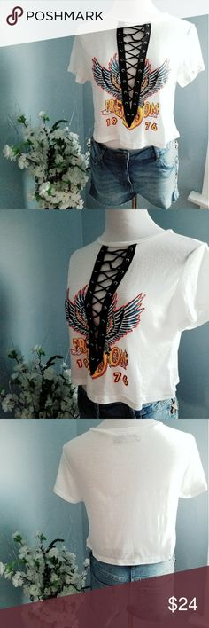 """FREEDOM Rock N' Roll Lace Up Cropped Graphic Top 50% POLYESTER, 38% COTTON, 12% RAYON Made in USA Calling all wild childs and rocker girls! This adorable cropped graphic tee features short sleeves, a black V-neck lace up detailing at chest with silver grommets, a """"Freedom - 1967"""" graphic at front, and a loose flowy cropped hemline. Looks awesome with the KOURTNEY lace up wet look leggings.  Small measures L: 17"""", B: 36"""", W: 40"""", 1"""" difference between sizes  Size small and medium Bella Edge…"""