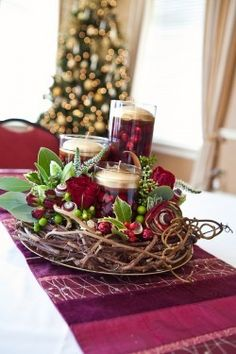 Christmas ~ Centerpiece ~ The main elements are just a large plate with a grapevine wreath on top, and three cylindrical glass vases in graduating sizes.  Add fresh cranberries with water and a floating candle to each vase and some holly sprigs and it's done!