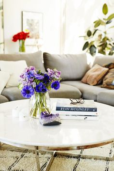 Marble coffee table with photography books, Amethyst agate, and flower vase.