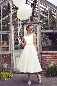 This simple rustic wedding dress is perfect for a relaxed country wedding. Elegant a-line wedding dress accenting with beaded on the sleeveless bodice matches with tea length skirt.