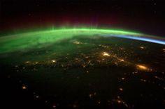 北アメリカの太平洋岸北西部を覆う柔らかな緑色のオーロラ。国際宇宙ステーション(ISS)に滞在する宇宙飛行士が撮影した。緑色のオーロラは、地上100キロ付近の低高度で発生。300~500キロまで高度が上がると、赤一色に発光する。写真右側には、オーロラの下に青みがかった輝き「大気光」も確認できる。高層大気中の原子や分子が太陽紫外線を受けて発光する現象である。  Photograph from NASA via AFP/Getty Images