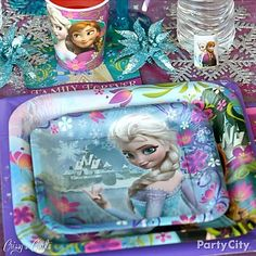 Set a place-setting fit for Arendelle royalty, with glittery snowflakes as coasters and accents on your Frozen party table. Click for more #Frozen party ideas!