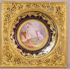 "SEVRES PORCELAIN PLATE. Cobalt rim with gilt decoration. The center has a hand painted courtship scene between a young man and a shepherdess. Artist signed ""A. Nicolas"". Late underglaze blue Sevres mark. 9 1/2""d. Ornate gold painted frame with easel back. 13"" x 13""."
