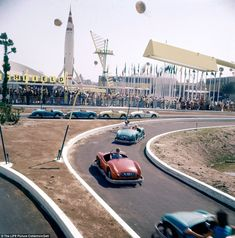 Popular attractions: Huge queues watch as children ride in colourful cars round a track flanked with a giant rocket