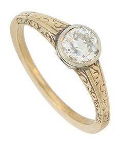 Ribbons of curling engraving embellish the sides and shoulders of this 14K yellow gold antique engagment ring. The elevated white gold central mount presents a luminous .40 carat, H color Vs2 clarity round cut diamond. The Art Deco ring measures 5.47 mm in width. Circa: 1930. Size 5 1/4.
