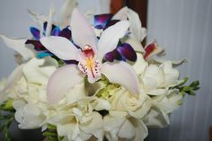 White cymbidium orchids with blue dendrobium orchids, white roses and finished with white freesia