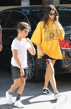 Making moves: Kourtney did wear a pair of tiny shorts and added a pair of black Adidas Gazelle trainers to the leggy look