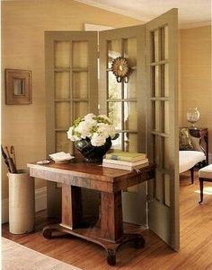 "In case you hate having the entrance right into your living room, add a screen divider and a table for an instant ""foyer"".old doors hinged together make a wonderful divider. Room Divider Doors, Room Dividers, Divider Screen, Screen Doors, Room Screen, Partition Door, Partition Ideas, Living Room Divider, Creating An Entryway"