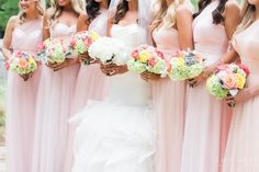 Brides in mismatched long light pink dresses with colorful bouquets posting with bride before October fall wedding in Dallas, Texas - Photos by Amy Karp Photography