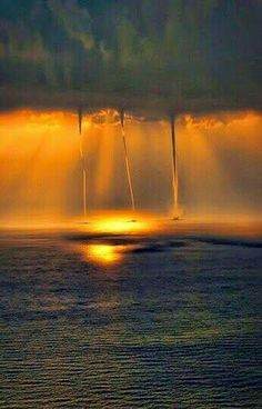 Waterspouts over the ocean at sunset.