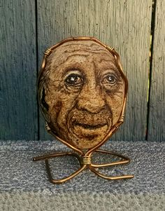 Merle Rockafella is a hand painted stone character. Wire wrapped to sit upright on shelf or table. One of a kind artwork