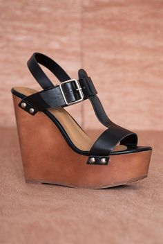 Renew your wardrobe in these black faux leather platform wedge sandals With a strappy design including a t-strap vamp and a buckled ankle strap these open toe sandals can be worn all season long