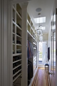 LA Closet Design - Narrow closet with built-in shoe shelves, drawers, sky lights and glass pendants.