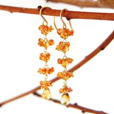 Tangerine orange Padparadscha sapphires with just a hint of pink cascade over faceted citrine to create these vibrant earrings. Each of the petite sapphires are poised on individual headpins, hand-linked, one by one, to crown each richly hued citrine gemstone, tumbling down to sparkling, microfaceted citrine teardrop b