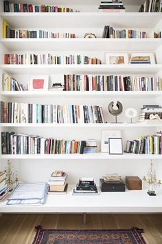 White shelving on a white wall, with loads of storage for books