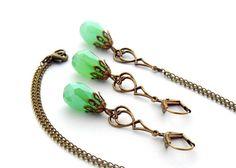 Filigranes Schmuckset, bestehend aus einer zarten Gliederkette mit Anhänger, bestehend aus einem Glastropfen in zartem Grün einen bronzefarbenen Ar...