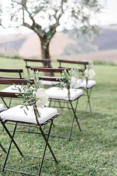 elegant ceremony aisle markers made of white peonies and olive branches