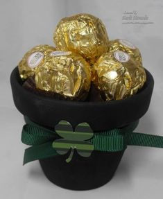 clay pot painted black with gold wrapped chocolates as place setting