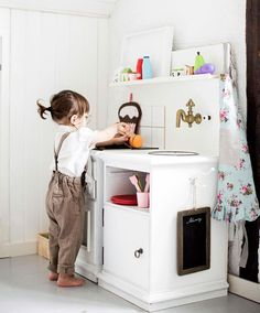 """Julie lagar mat i köket som mamma har byggt. En vit palett bildar färgbas i rummet, med tanken att Julie själv lätt ska kunna sätta egen prägel på rummet när hon blir äldre. De flesta av möblerna har Lina och pappa Joakim köpt second hand, några har Julie fått ärva. """"Jag tror man kan räkna allt vi har köpt nyproducerat på en hand"""", säger Lina."""