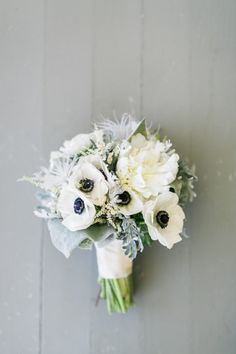 White bouquet with anemone and feathers: http://www.stylemepretty.com/california-weddings/san-luis-obispo/2014/11/18/chic-summer-ranch-wedding/ | Photography: Mirelle Carmichael - http://www.mirellecarmichael.com/
