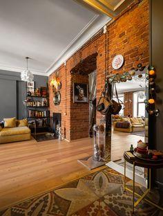 Квартира скирпичными стенами иразноформатной мебелью напоследнем этаже дореволюционного дома