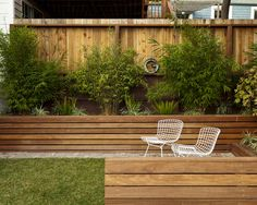 beautiful landscape exterior with wooden retaining walls and patio furniture