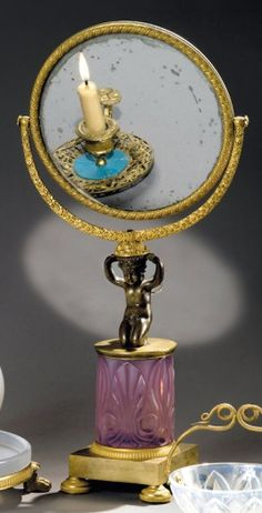 GLACE DE COMMODE A double face, foncé de miroir au mercure, dans un encadrement de bronze ciselé et doré à fleurs et feuillages. L'ensemble est soutenu par un amour agenouillé, reposant sur une colonne en opaline gorge de pigeon, présentant des fleurs de lys, stylisées. Socle quadrangulaire à petits pieds patins à palmettes, graine et grattoirs. Époque #CharlesX. - Piasa - 15/05/2009