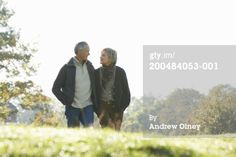 Stock Photo : Mature couple walking through countryside, smiling at each other