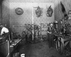 Bicycle repair shop :: Western History | Interior view of a bicycle repair shop in Denver, Colorado; shows men, a workbench, tools, and posters of women. Date[between 1905 and 1910?]