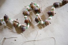 (*A note about acorn crafting. I prefer to bake the acorns for an hour at 180 in the oven, to kill the grubs inside, rather than having them fall out as the acorns age. And we use a small drill bit to make holes in them, easy for stringing.)