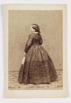 """The pose with the subject facing away from the camera is suggestive of full mourning, however the layers of """"ruffles"""" on her skirt suggest she's been in this state for several months at least."""