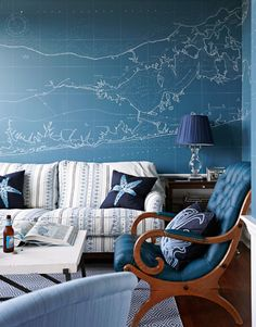 """Map Room - For the walls of the """"map room,"""" artist Lori Barnaby painted a nautical chart of Long Island in the style of a blueprint. """"In keeping with the theme,"""" says designer Kim Coleman, """"the blues of the sofa, chairs, rug, and accessories create an aquatic aura."""" Barclay Butera Carmel sofa. Dash & Albert Diamont Denim Rug. Ankasa pillows. Visual Comfort lamp. An antique library chair is covered in Edelman leather."""