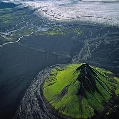 MOSS ON A CONE - Aerial Photography by Bernhard Edmaier - Over the centuries, the extinct volcanic cone of Mælifell, near the glacier Myrdalsjökull, south Iceland, has been released from the grip of the ice. Approximately 100 metres high, its slopes now proliferate with green spring moss, and glacial water flows around its base. #iceland #glacier