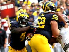 Michigan #4 De'Veon Smith runs through the hole teammate #52 Mason Cole created for him during first half action at Michigan Stadium in Ann Arbor, Michigan on Saturday, September 19, 2015. Michigan won the game 28-7