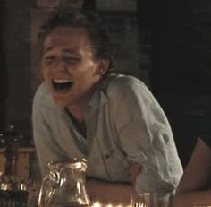 HE LOOKS LIKE HE IS LAUGHING AT A DIRTY JOKE THAT HE ACTUALLY FOR ONCE UNDERSTOOD BUT HE FEELS GUILTY FOR ENJOYING IT