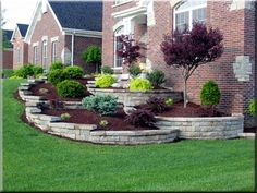Use of hardscaping retaining walls with this landscape design is an effective way to handle the side sloping lawn.