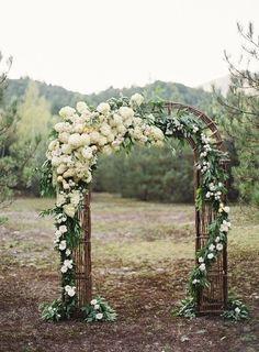 Love the flower bursts (hydrangeas?) on this wedding arch! <3