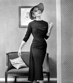 Model in navy wool dress, long-sleeved, draped across the hips ending in panel on the back by Pierre Balmain, photo by Philippe Pottier, 1955