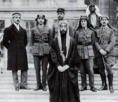 Emir Faisal's party at Versailles, during the Paris Peace Conference of 1919. Left to Right: Rustum Haidar, Nuri as-Said, Prince Faisal (front), Captain Pisani (rear), T. E. Lawrence, Faisal's Slave (Name Unknown), and Captain Hassan Khadri.