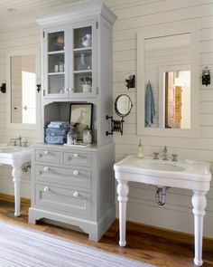 With its carved feet and white knobs, the towering gray cabinetry brings all the charm of an antique step-back cupboard with the sturdiness of a modern built-in. On each side, curvy ceramic sink consoles and simple framed mirrors keep the room light and fresh.