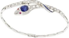 Art Deco Sapphire, Diamond, Ruby, Platinum Bracelet  The bracelet features a cushion-shaped sapphire measuring 6.60 x 5.40 x 4.98 mm and weighing approximately 1.40 carats, enhanced by European and single-cut diamonds weighing a total of approximately 0.80 carat, accented by square and tapered baguette-cut synthetic sapphires, highlighted by ruby cabochon eyes measuring 1.50 mm, set in platinum