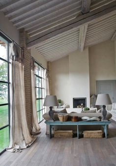 Light and bright. Vaulted painted ceilings to keep it soft and cozy soft linen drapes and sofas. Rustic accessories and floor. Lots of windows!