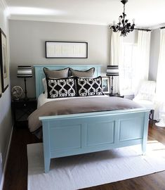 Gray white and black room with aqua blue painted wooden bed. This is a good way to turn a traditional bed into something a bit more modern. TIP: Bed linens tie in with the room's colors.