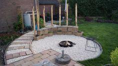 Zitmuurtje bij de vuurplaats, met een 'rugleuning' van verticale kastanjehouten palen. Foto en tuinontwerp: Vicas Tuinontwerpen www.vicas.nl