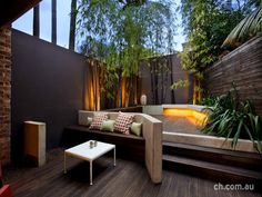 I think this has potential for a spa. There are several things I love about this space... the bench for one!  The minimalist plantings still make a great statement and the dark walls to match the wood is perfection.  The lighting really makes this space!