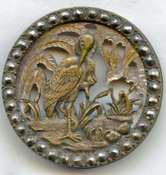 Pegs Button Blog--Stork, pearl and brass button.  A finely detailed, stamped, silvered and pierced design mounted over a carved and pierced pearl background. There is a second bird carved into the the pearl background, at right. The steel-set, brass rim is applied over the pearl background.