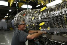Production assembly mechanic Howard Shanor works to hang a gearbox on a CF6-80C2 jet engine at General Electric Co.'s GE Aviation factory in Cincinnati, Ohio, U.S., on Wednesday, June 25, 2014. The Institute for Supply Management (ISM) is scheduled to release U.S. manufacturing figures on July 1. Photographer: Luke Sharrett/Bloomberg via Getty Images #aviationmechanic