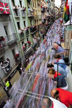 Revelers run on Estafeta street beside to Fuente Ymbro fighting bulls ranch as people look on from balconies above, during the fifth running of the bulls in Pamplona Spain on July Best Places To Live, The Places Youll Go, Cool Photos, Beautiful Pictures, Interesting Photos, Pamplona Spain, Running Of The Bulls, World Images, Gap Year
